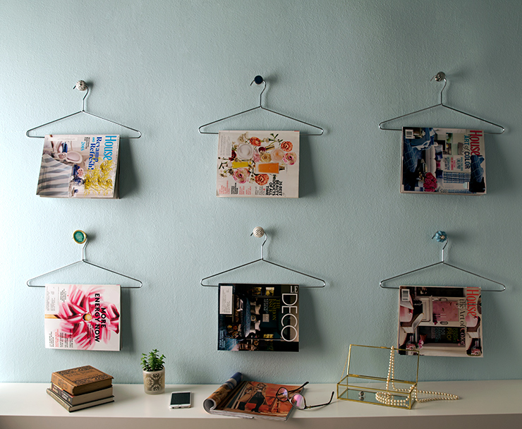 This image shows a wall painted in Peek a Blue. On the wall are six silver chrome hangers hanging on dresser door knobs. On the hangers are magazines. This is a creative feature wall to show off magazines.  Below is a white console with books, a plant, cell phone, opened magazine, glasses and a jewelry box.