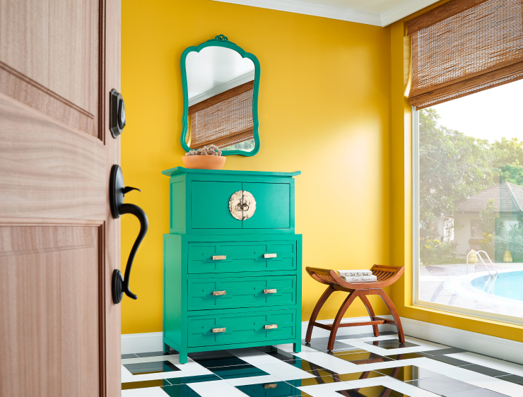 An undescriptive room with am aqua colored dresser and walls painted in English Daisy.