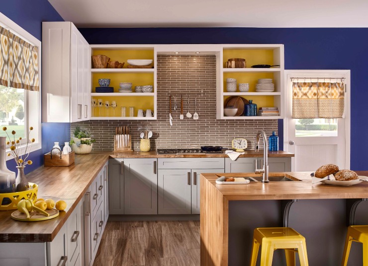 A kitchen with walls painted in a bright navy blue and accents are in yellow.