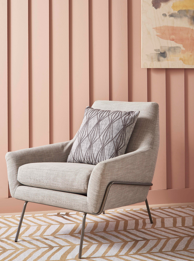 A chair sitting in front of a paneled wall painted in Flamingo Feather