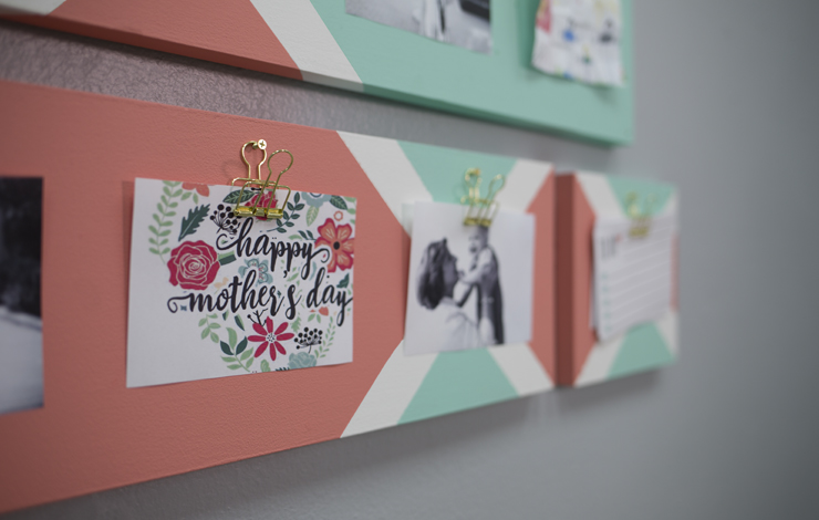 The finished decorative clipboard mounted on a wall with pictures hanging from it.