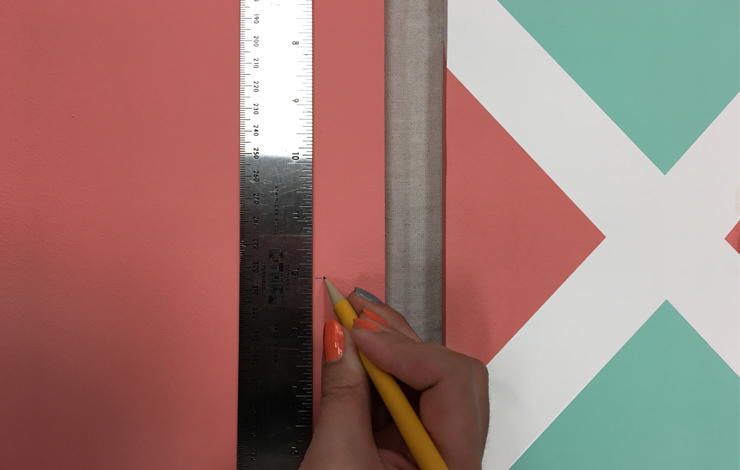 Person with ruler and pencil marking off a section on the board.