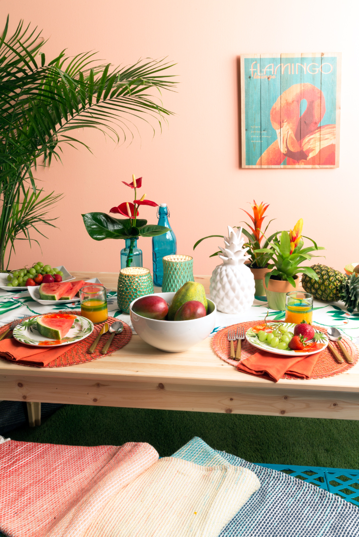 An exterior dining setting decorated with coastal or casual decor and Flamingo Feather painted wall.