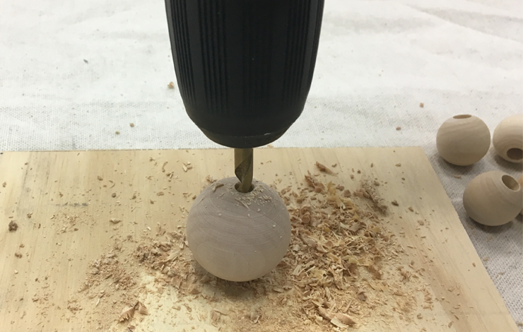 Drilling a hole into a small wood ball.