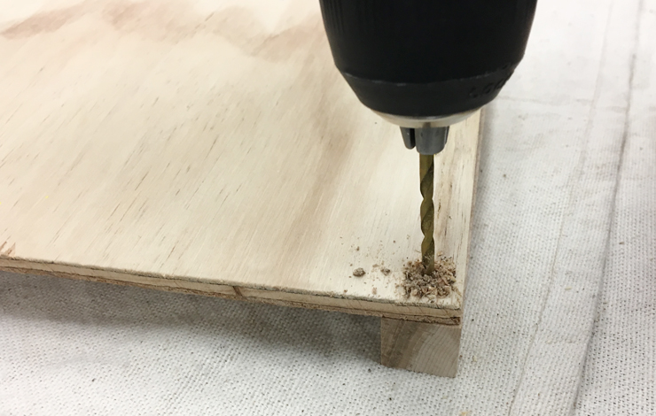 Using a drill to make a hole in the wood.