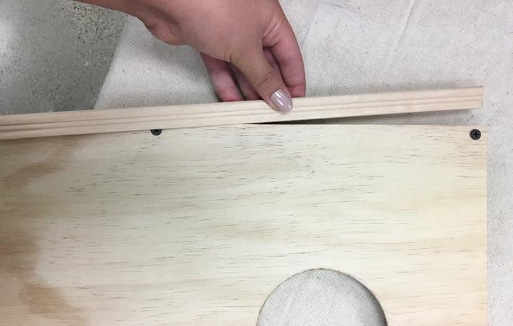 Placing wood trim onto the flat wood board.