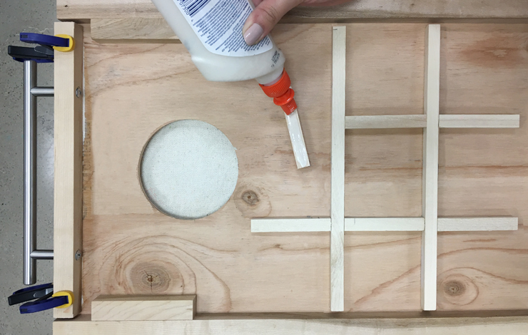 Adding glue to small strips of wood and placing on board.