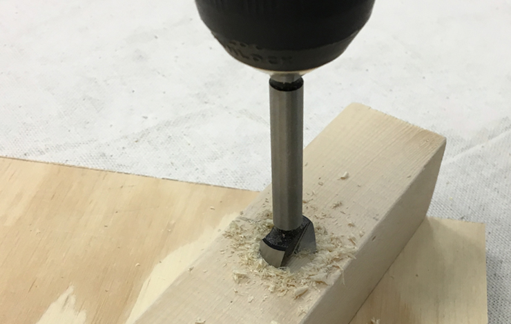 Drilling a hole in the wood board.
