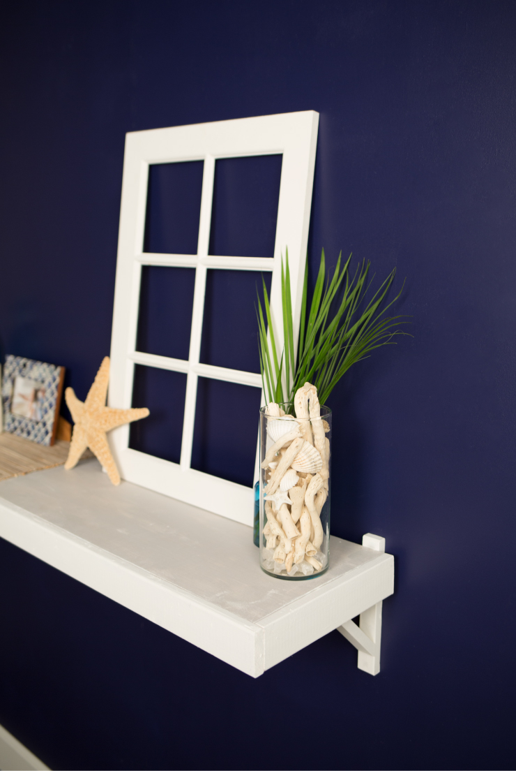A wall painted in a deep purplish-blue color, Bon Nuit. On the wall is a white shelf decorated with beach décor.