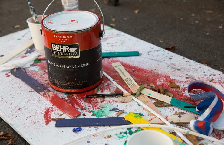 A drop cloth with a gallon of Behr Premium Plus exterior flat paint,  dipped paint sticks, paintbrush, pencil.
