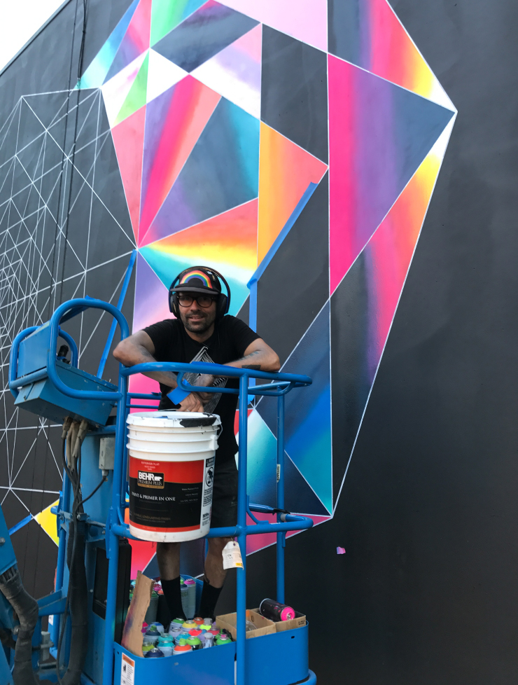 An artist posing in front of his mural that he is painting.