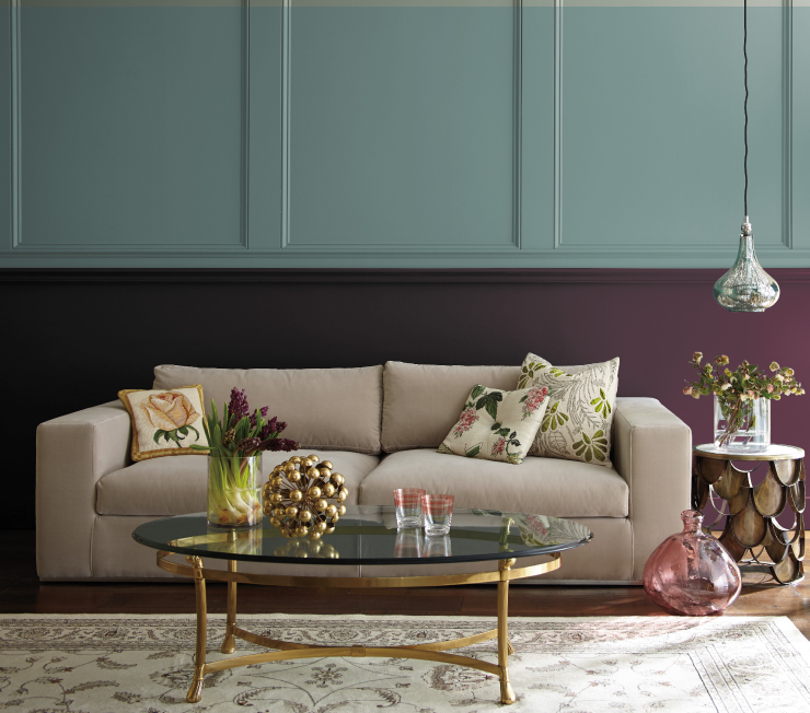 A living room with the bottom half of the wall painted in a plum/purple color. The top half is paint in the color: In The Moment.