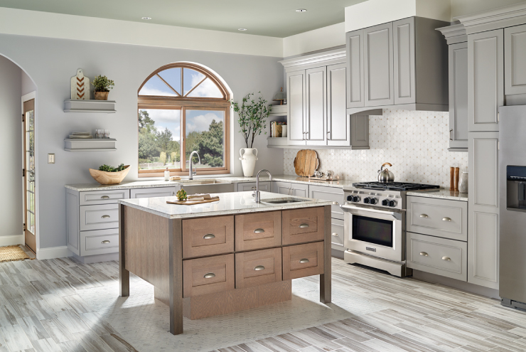 A kitchen painted in a gray color, cabinets are the same color. Trim is white.