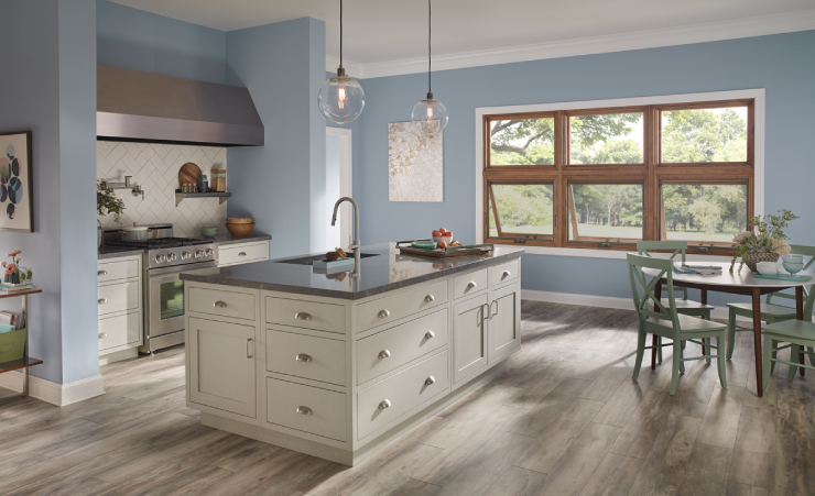 A kitchen painted in a light blue color with cream colored cabinets.