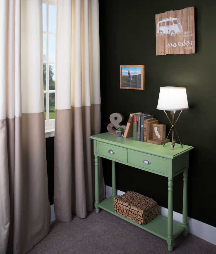A corner of a room showing a side table against the wall. The area is decorated in a travel theme. The walls of the area are painted in Unplugged.