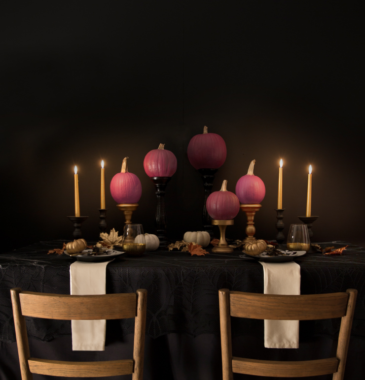 A dinner table set for two for dinner. Table is dressed in cob webs draped on top of a black table cloth. Pumpkins painted in wine and purple colors are placed on gold and black candelabras.  Lit candles, smaller painted pumpkins, and gold painted leaves set the ambiance.