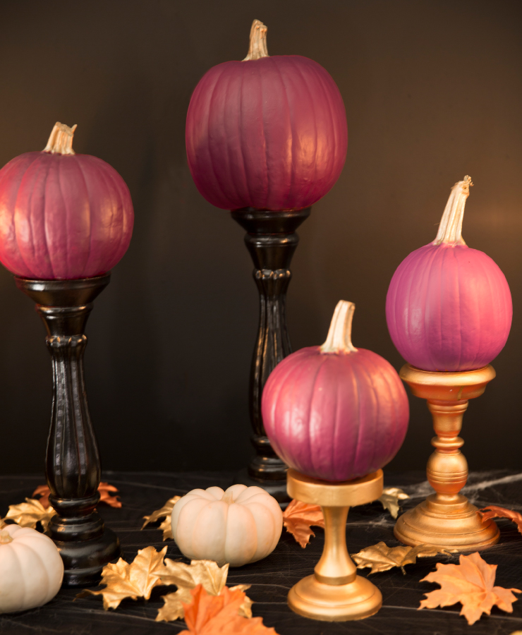 A close up view of the candelabras with pumpkins sitting on them.