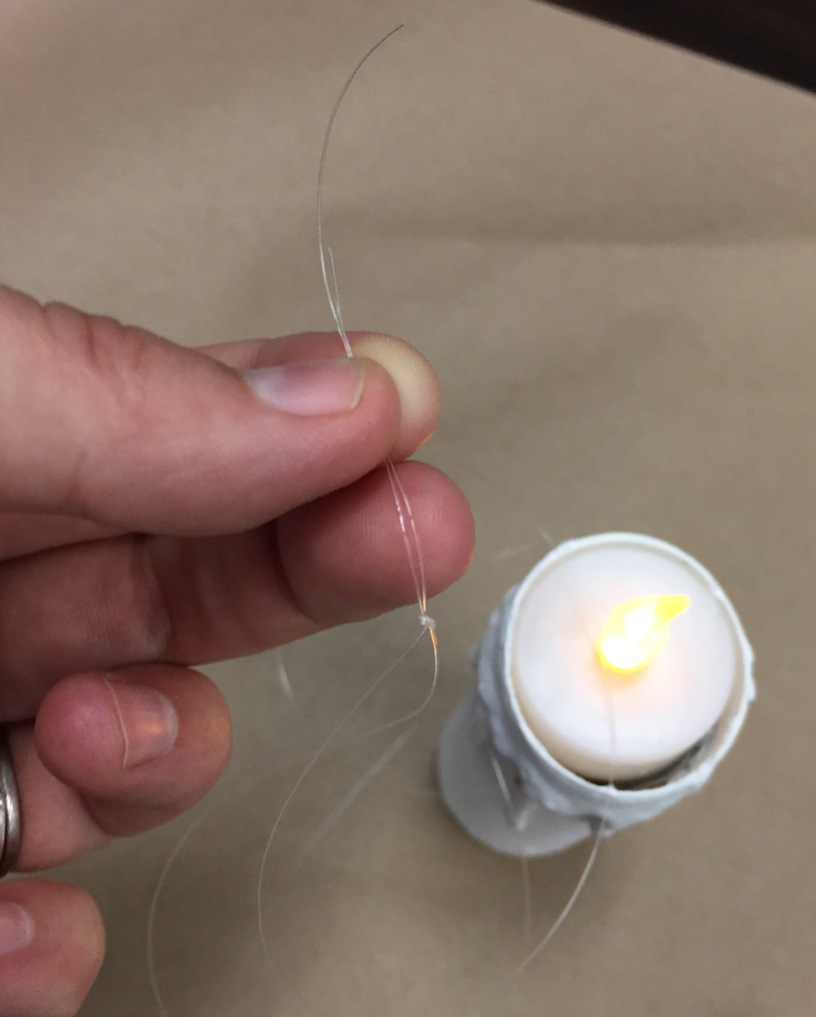 Showing a tied knot at the end of the string that is attached to the carboard roll with a battery-operated candle added at the top under the string.