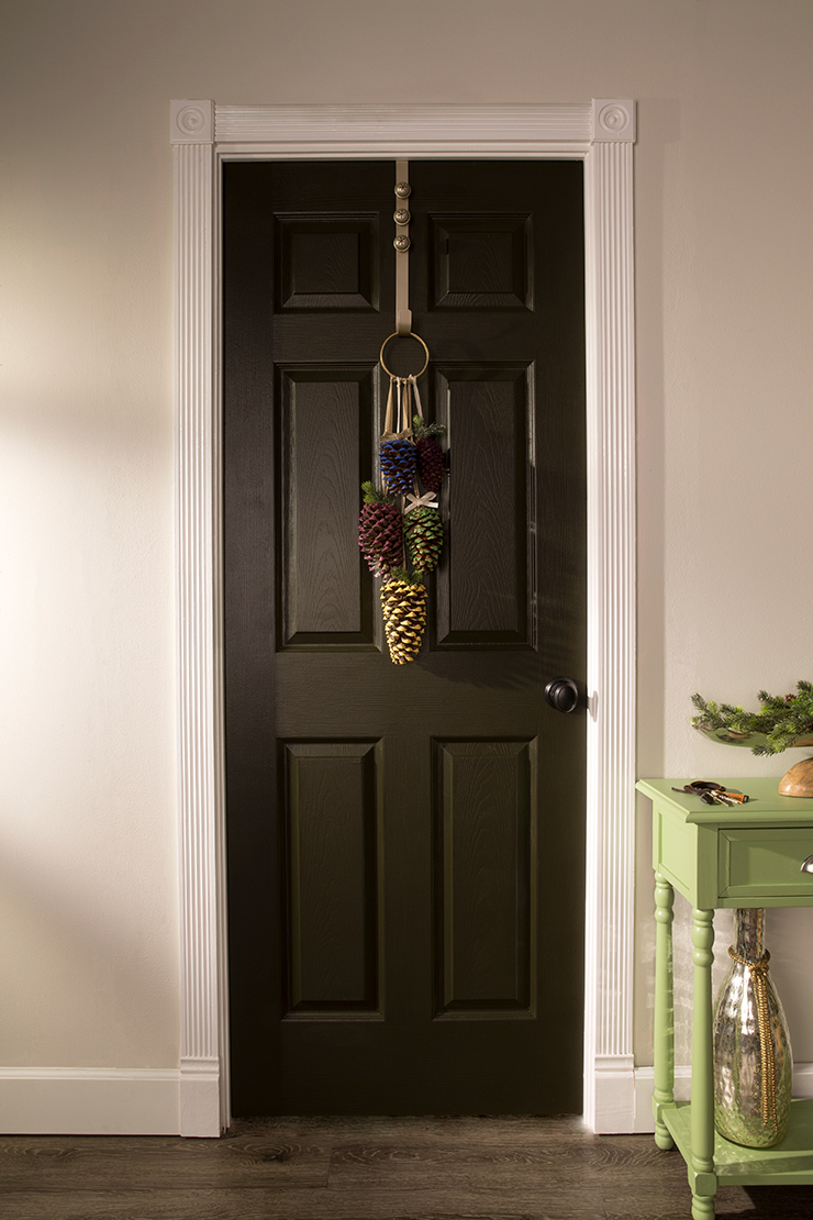 This image is of an interior door painted in Unplugged.  It is decorated with painted pinecones hanging on the door with a door hanger.  To the right of the door is a green console with keys peaking through and a branch of pine needles.  Also a large vase on the bottom shelf of the console.