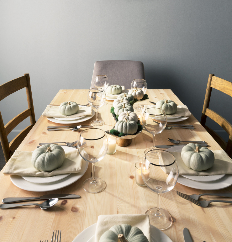 A holiday table setting  featuring painted pumpkins in a light dusty green paint color.