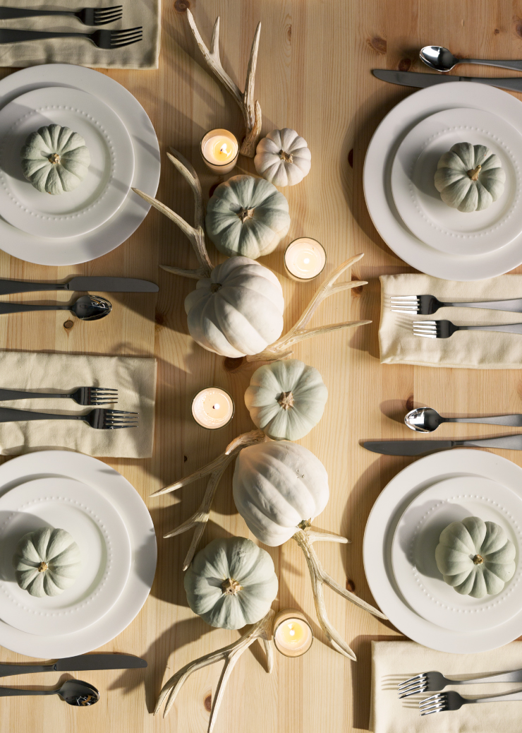 A top view of fall holiday table setting featuring painted pumpkins.