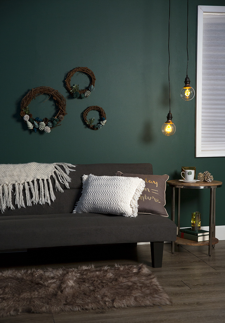 This image shows wall painted in Equilibrium. The wall is decorated with our DIY pinecone wreaths.  Below the wreaths is a sofa furnished with a blanket and pillows. To the right is a wooden side table with a cup of tea, books and a small light.  There are also hanging light bulbs from the ceiling.