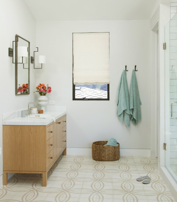 A bathroom painted in Soft Focus. Furniture is yellow toned wood. Green towels hang from the wall.