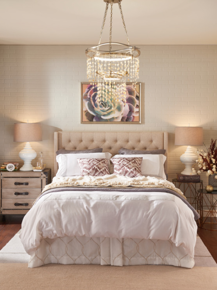 A bedroom with brick walls painted in Soft Focus. The furniture is a light wood color and bedding is white with neutral pops of color.