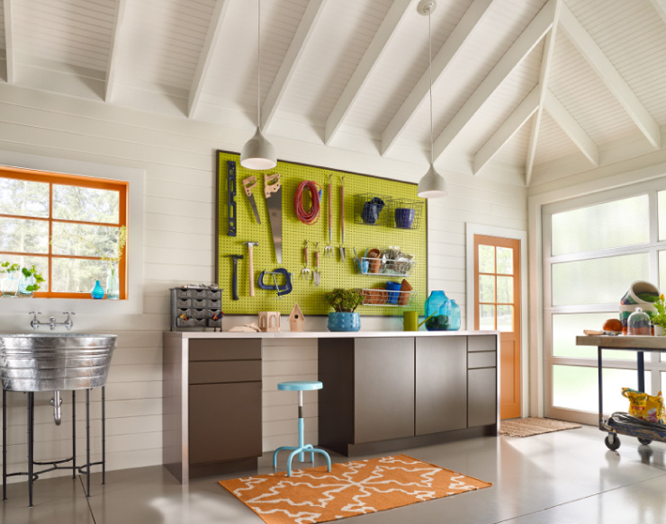 A garage work area painted in Soft Focus. The area is bright with windows. Is decorated with pops of bright orange and green accessories.