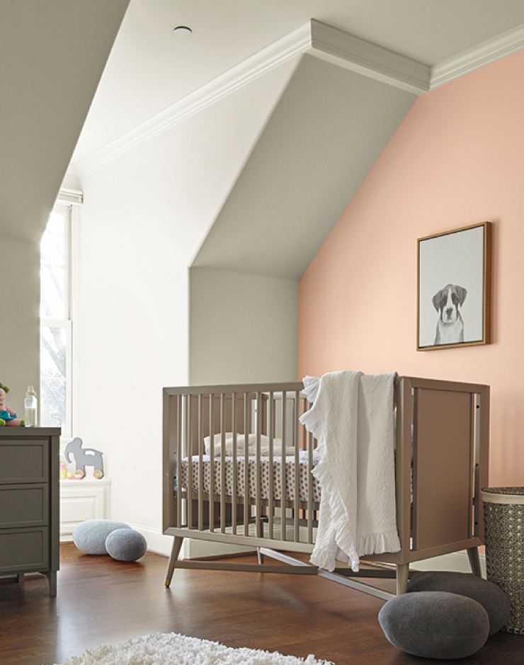 A nursery with vaulted ceilings painted in Soft Focus. One wall is painted in a soft pink color. Accessories in the room are wood tone and gray colors.