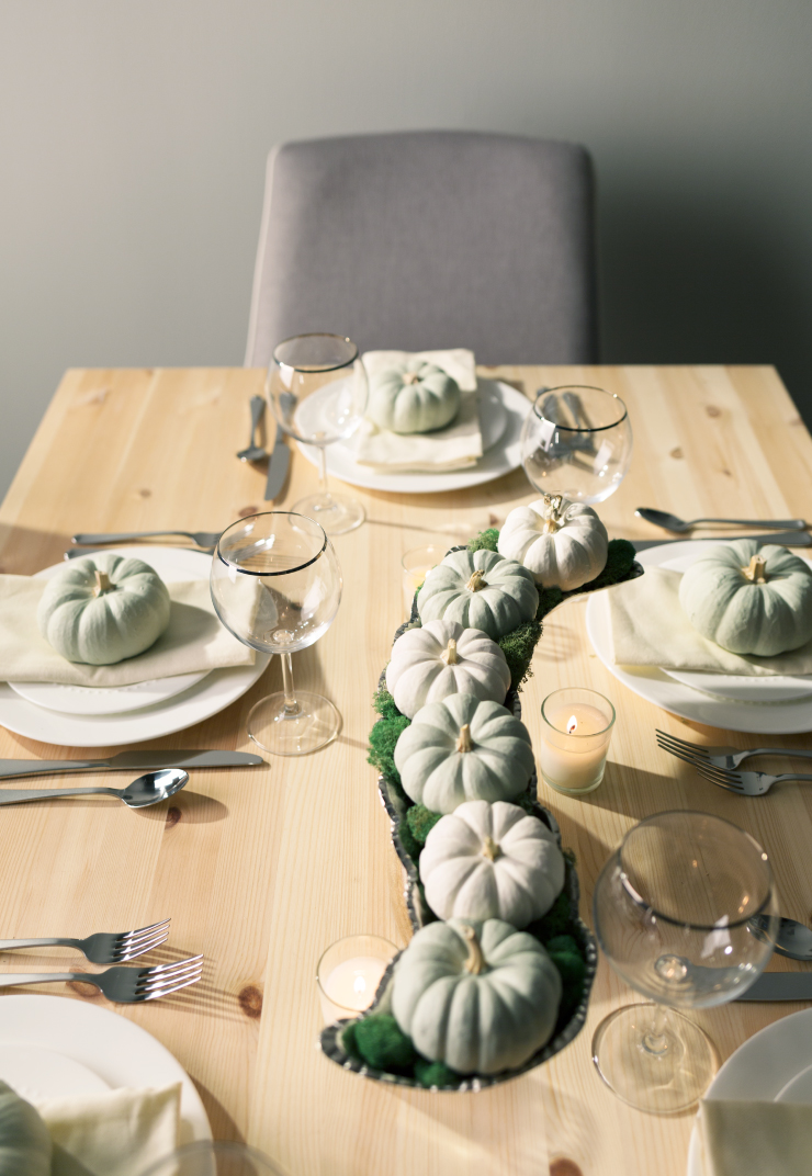 A close detail of holiday table setting with a serpentine shaped center pieces, decorated with painted pumpkins.