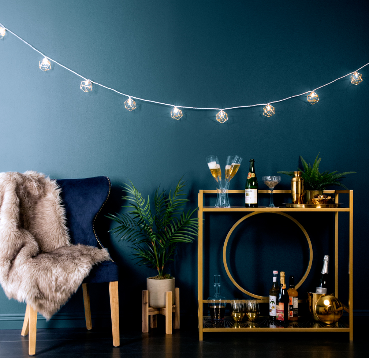 A sitting area with a deep blue velvet chair. In the chair is a dark cream colored soft furry blanket. Next to the chair is a liquor table with fun New Year's Eve drinks. String lights hare hanging from the wall. Wall is painted in color Midnight in the Tropics.