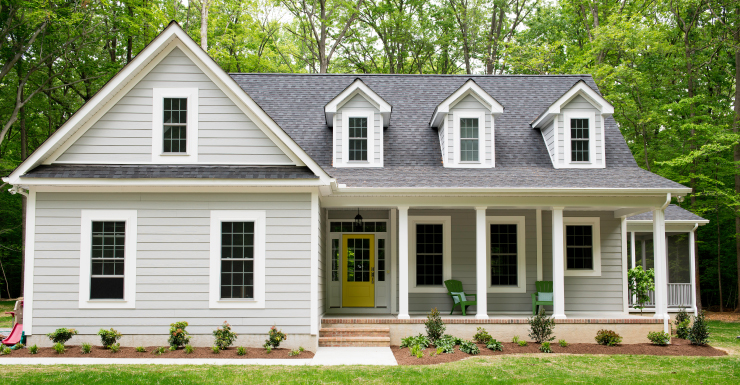 An exterior home painted in Quiet Time. The trim is white and front door is a bright yellow color.