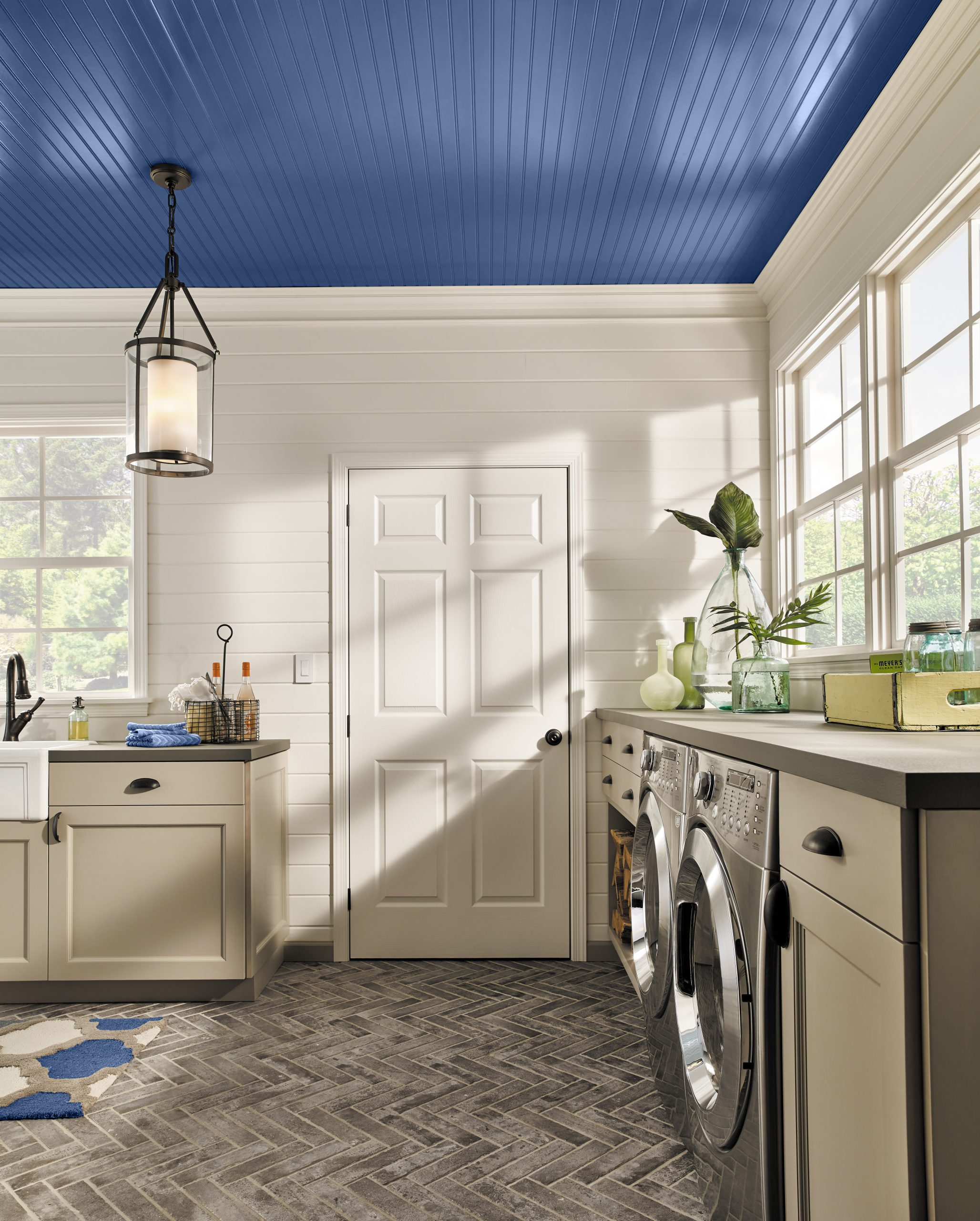 A large and well lit laundry room with a glossy painted blue ceiling.