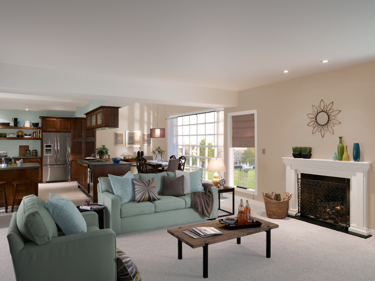 An open floor plan showing living room in the foreground, kitchen and dining in the background.