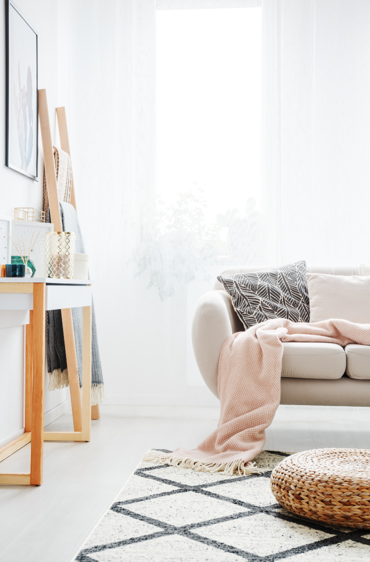 A living room painted in a white color with a light beige colored couch. A peach blanket is placed on the couch.