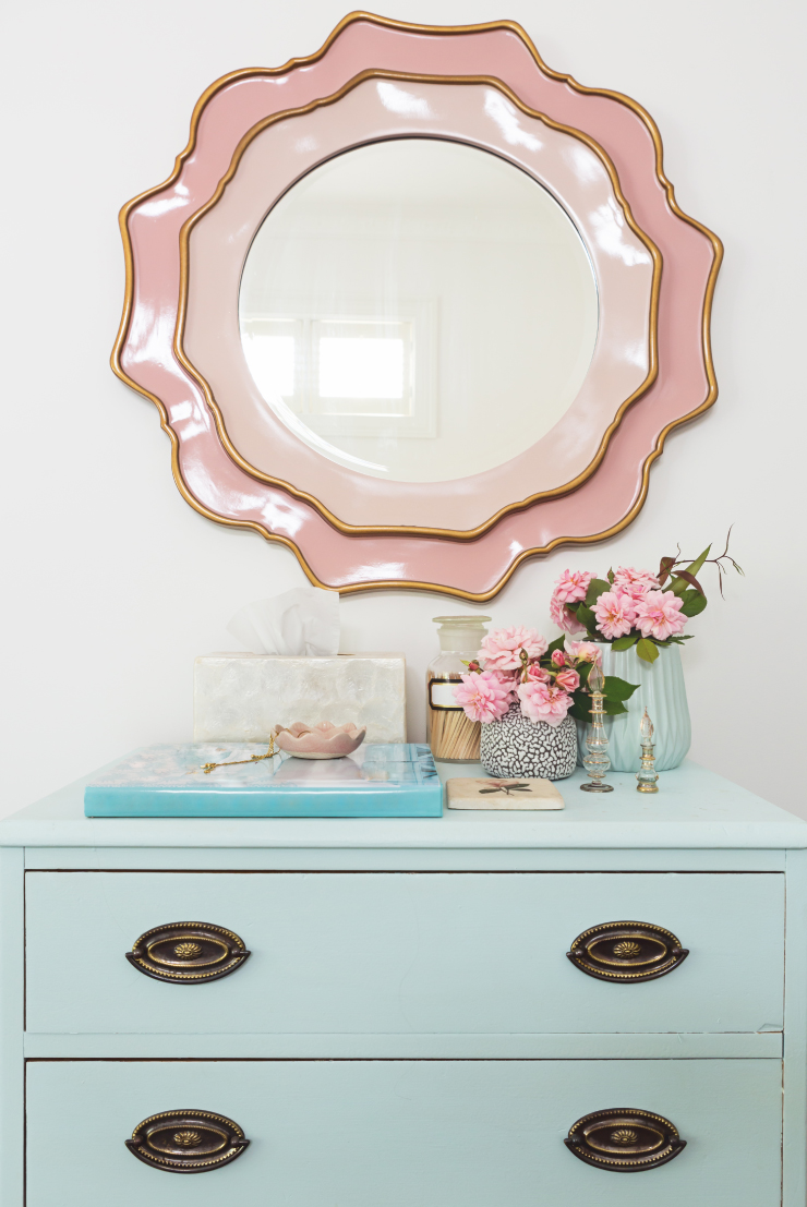 A dresser painted in a light blue color decorated with vases of pink flowers and trinkets. Above the desk is a scalloped edge mirror in a peach color.