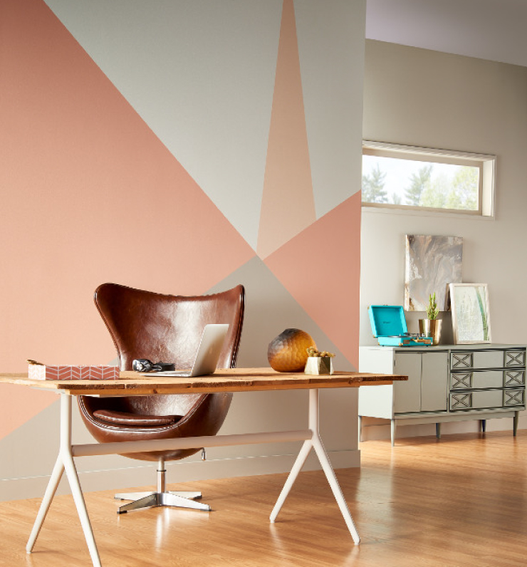 A tight view of the home office area and wall behind the desk that is painted using geometric shapes in soft gray and peach colors.