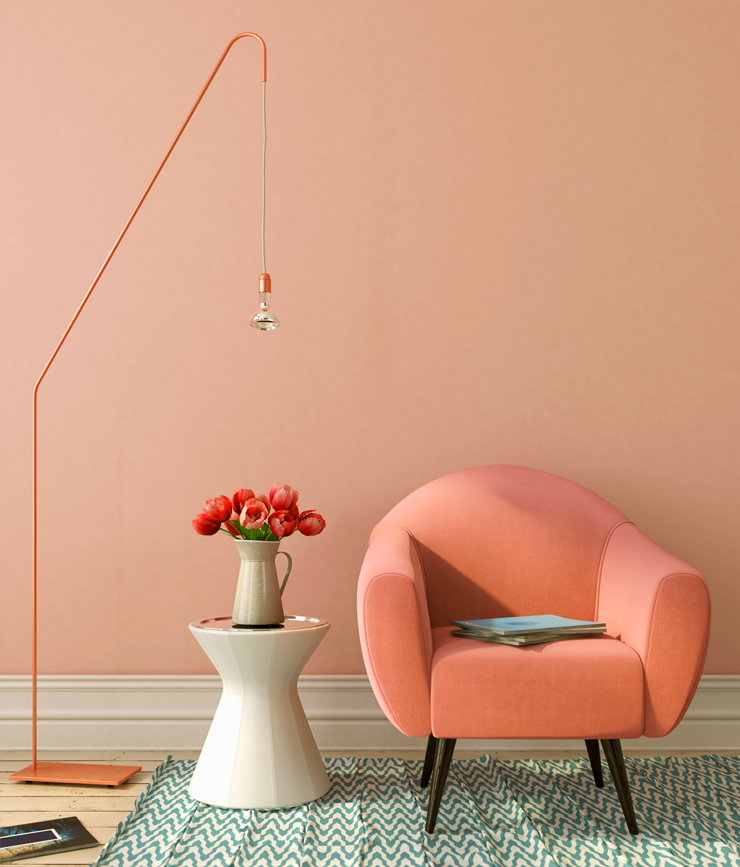 A sitting area with a cozy peach chair, side table with red tulips in a vase and a hanging light. The wall painted in Sunset Drive.