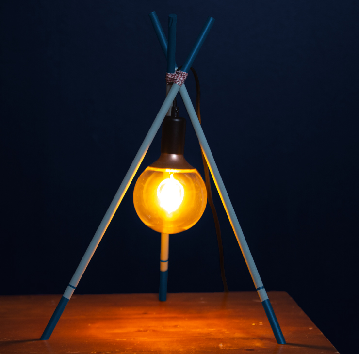 A picture showing a lit lamp that is shaped like a tripod sitting on a table