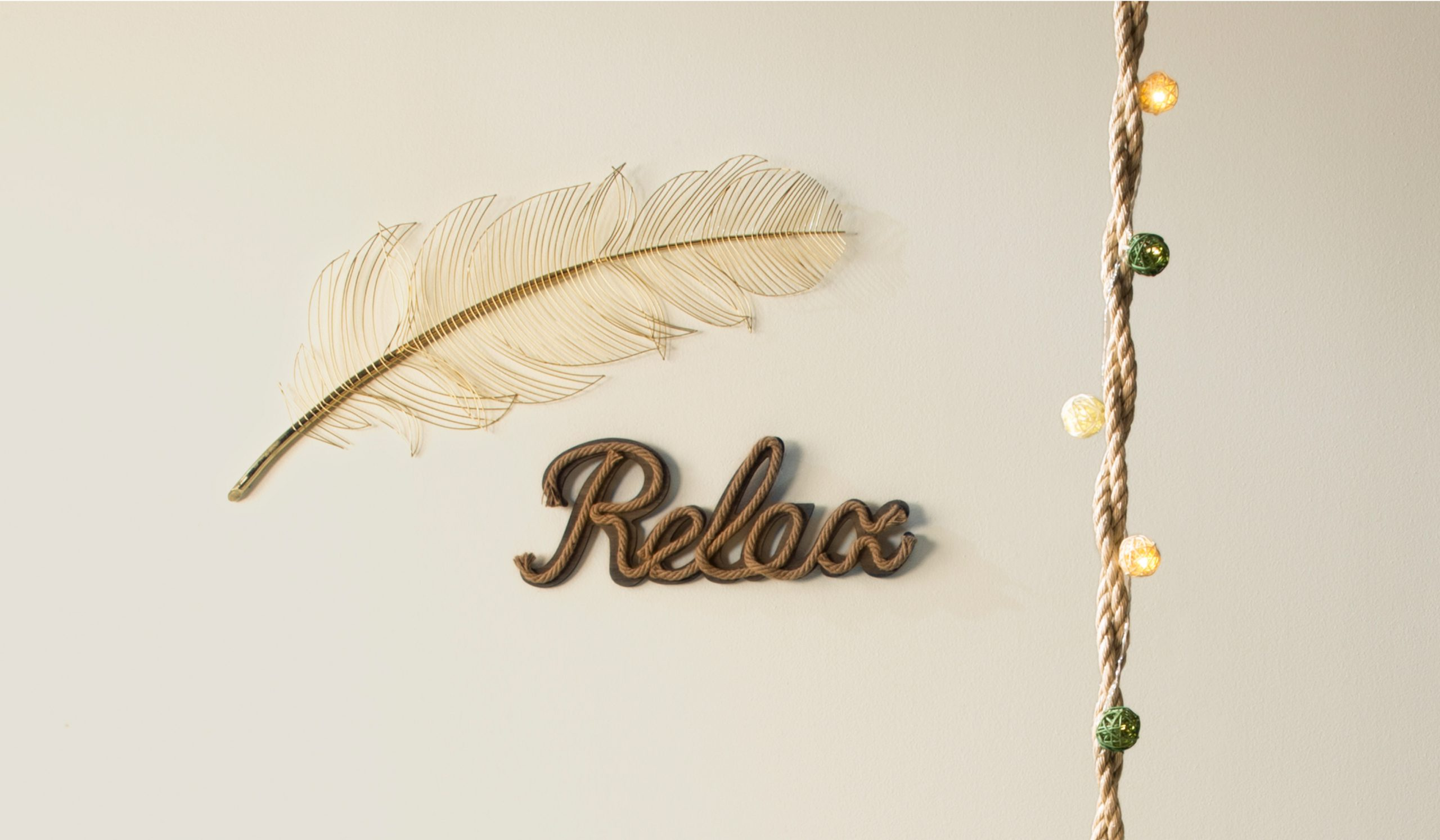 A tight crop of the wall showing a wire feather and a sign made from rope in the word relax. In the foreground you see the rope of the swing with yellow and green light balls wrapped around the rope.