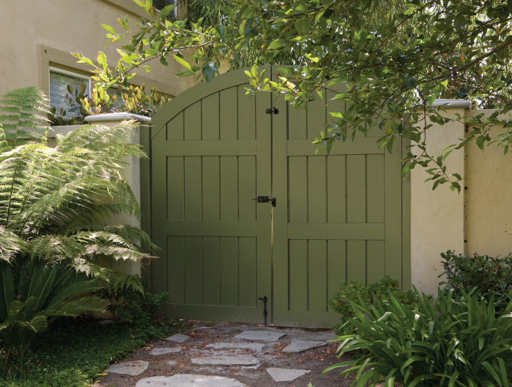 An exterior entry showing a pathway and gate into a yard. Color of gate is painted ion Secret Meadow.