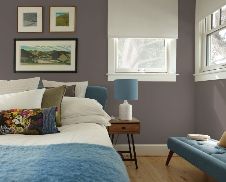 A bedroom painted in a grayish brown color with blues used as accents.