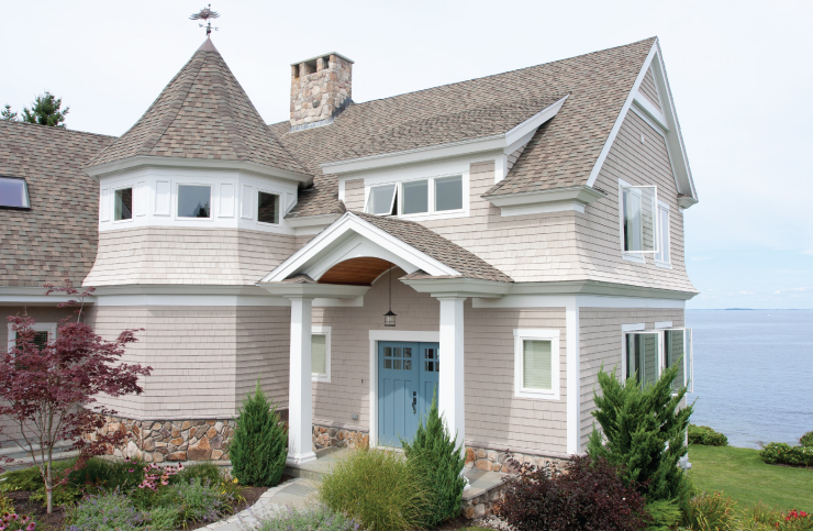 An exterior home painted in a neutral cream color with the accent door painted in Blueprint.