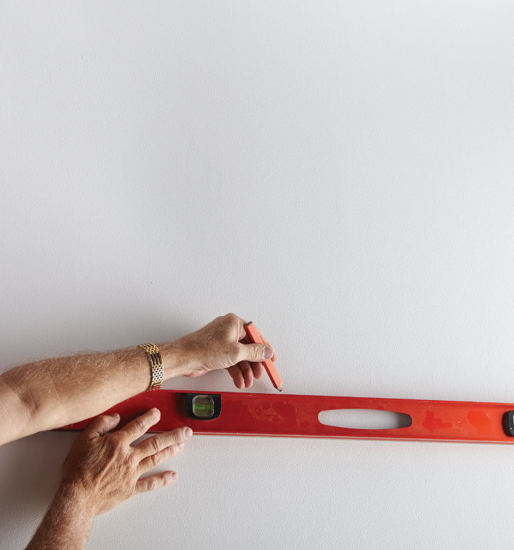 A person with pencil and leveler drawing a straight line on the wall.