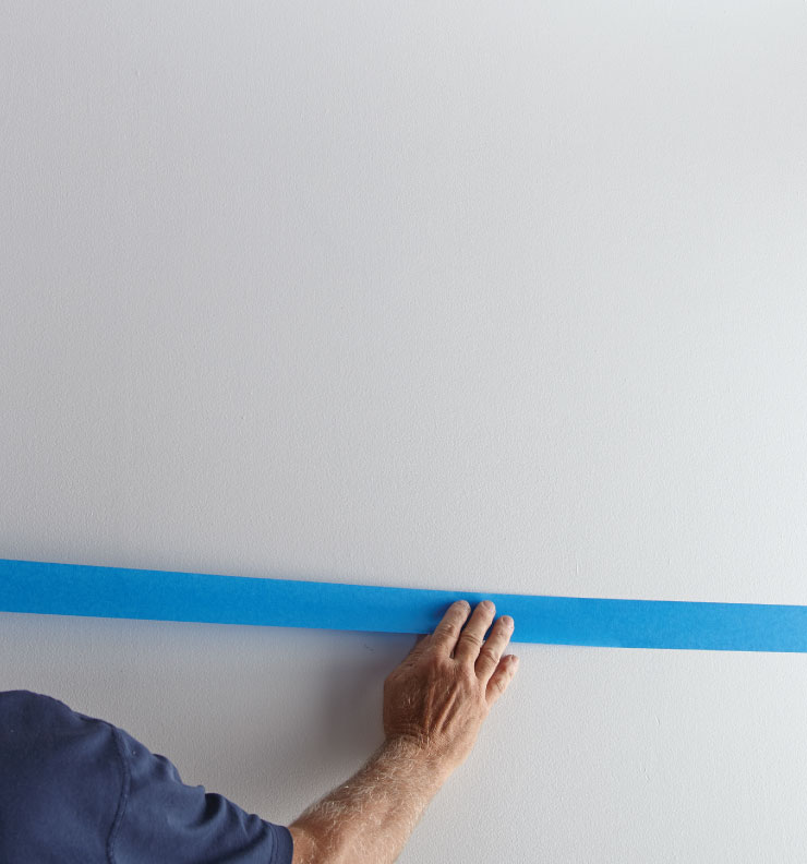 A person adding tape along the wall using pencil line as a guide.