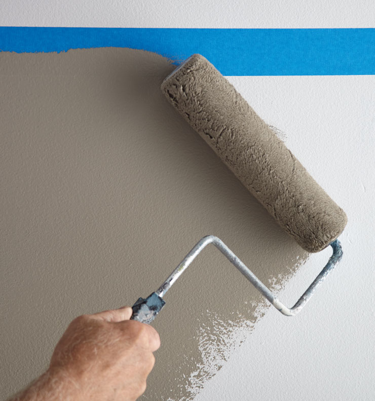A person applying gray colored paint in the area below the blue tape.