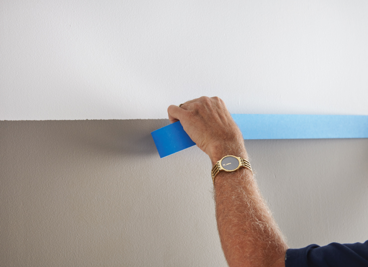 A person removing the blue tape from the wall that was painted.