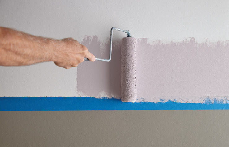 A person applying purple colored paint in the area above a new piece of blue tape.