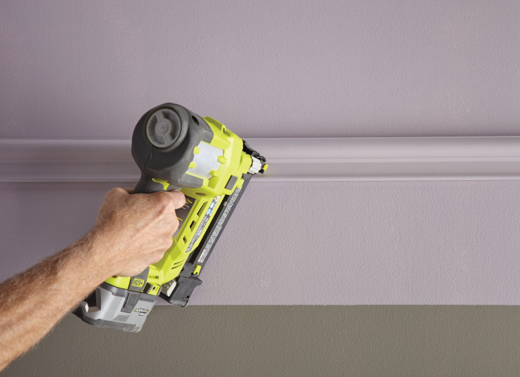 A person using a nail gun to adhere the purple trim to the purple wall.